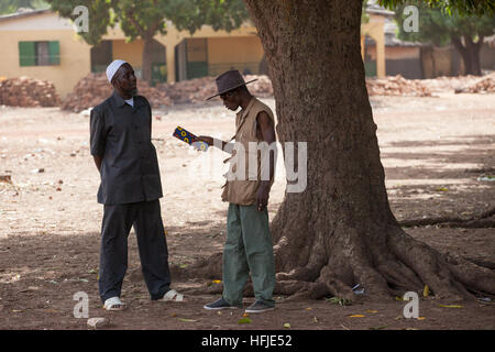 Baro village, Guinea, 1st May 2015:  Men chatting in the shade. - Stock Photo
