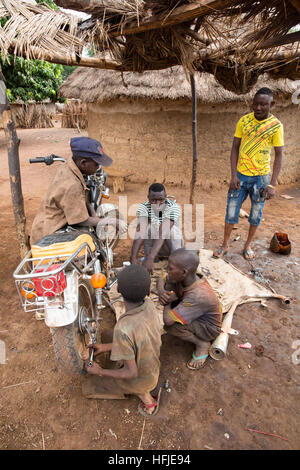 Gbderedou Baranama, Guinea, 2nd May 2015;.Young apprentices repairing a motorbike. - Stock Photo