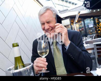 BUSINESSMAN MAN BAR WINE DRINK DRUNK ALCOHOL PROBLEM WORK CITY MAN HAPPY AFFAIR  Mature city businessman sitting - Stock Photo