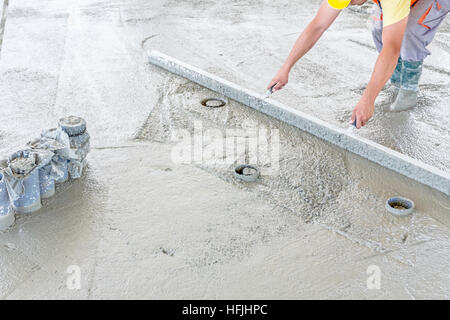 Mason is using a trowel to finish top of the concrete foundation. - Stock Photo