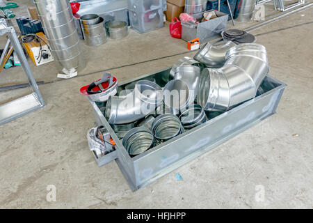 Metal box with pile of zinced ventilation pipes for air conditioning system is placed in metal pallet. - Stock Photo