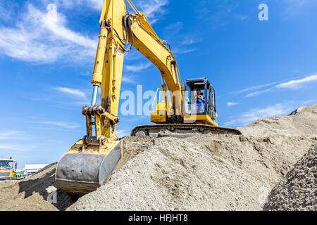 Yellow excavator is making pile of soil by pulling ground up on heap at construction site, project in progress. - Stock Photo