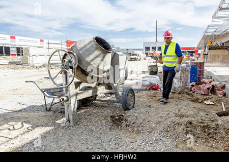 Zrenjanin, Vojvodina, Serbia - May 29, 2015: Cement mixer machine is at construction site with wheelbarrow, tools, - Stock Photo