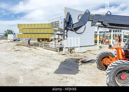Logistics concept, view on telescopic forklift that is carries composite panel walls at construction site. - Stock Photo