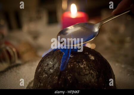 Christmas pudding with brandy alight on it - Stock Photo