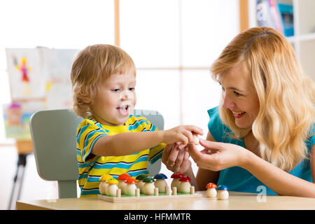 Mother and child learn color, size, count while playing with developmental toys. Early education concept. - Stock Photo