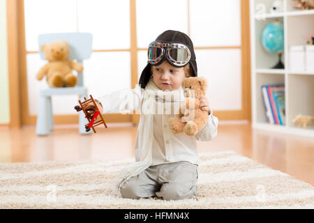 Happy kid boy plays with toy airplane at home in his room - Stock Photo