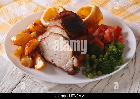 Sunday Roast: pork with potatoes, vegetables and Yorkshire pudding on the plate closeup. horizontal - Stock Photo