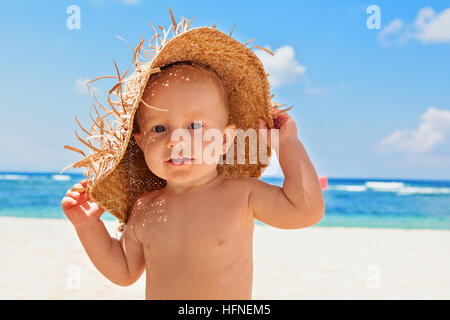 Funny happy baby boy on beach with straw hat, dirty face covered with sand. Family travel, healthy lifestyle, holiday - Stock Photo
