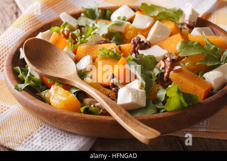 Fresh salad with persimmons, walnuts, arugula, cheese and oranges close-up. Horizontal, rustic - Stock Photo