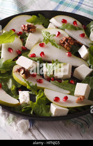 Fresh salad with pears, pomegranates, cheese, walnuts and greens close up on a plate. vertical - Stock Photo