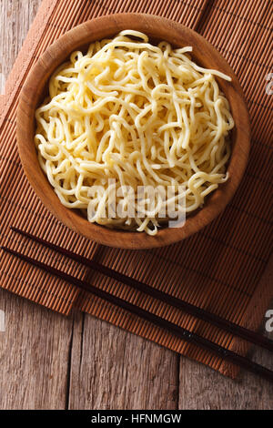 Asian ramen noodles in wooden bowl on the table. vertical top view - Stock Photo