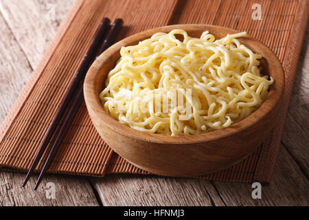 Asian ramen noodles in wooden bowl close-up on the table. horizontal - Stock Photo