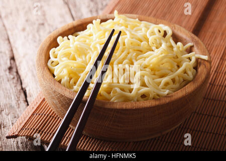 Asian fast food: Ramen in a wooden bowl on the table close-up. horizontal - Stock Photo