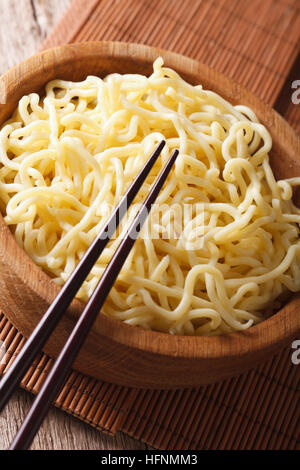 Traditional Asian ramen noodles in wooden bowl close-up on the table. vertical - Stock Photo