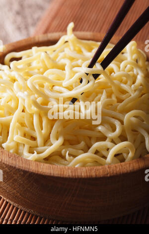 Asian Food: Ramen noodles macro in a wooden bowl on the table. vertical - Stock Photo