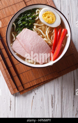 Asian Food: Ramen noodles in broth with pork, vegetables and egg in a bowl close up. vertical top view - Stock Photo