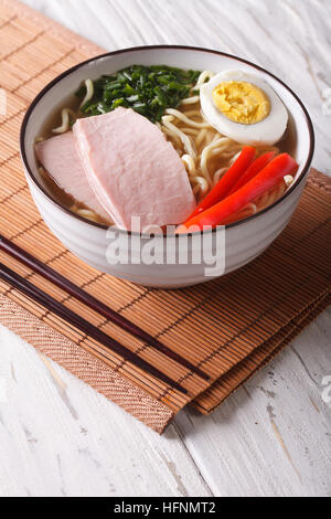 Ramen noodles in broth with pork, vegetables and egg in a bowl. vertical - Stock Photo