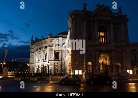 Beautiful view of historic burgtheater imperial court theatre in the evening and cars on street, vienna, austria - Stock Photo