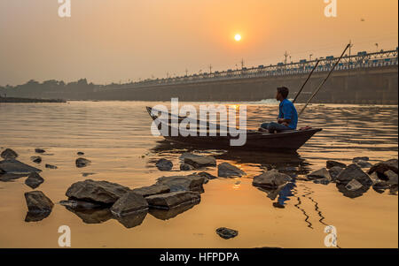 An oarsman sits on his boat at sunset on river Damodar near the Durgapur Barrage, West Bengal, India. - Stock Photo