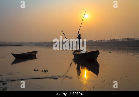 Silhouette boat with oarsman at sunset on river Damodar, Durgapur Barrage, West Bengal, India. - Stock Photo