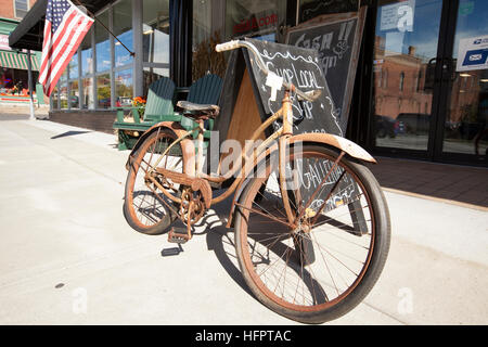 CANANDAIGUA, NEW YORK - OCTOBER 11, 2016: Rusty, old bicycleoutside of a consignment shop in the town of Canandaigua, - Stock Photo