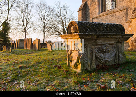 Holy Rood Church and tomb in the early morning winter sunlight. Shilton, Nr Burford, Cotswolds, Oxfordshire, England - Stock Photo