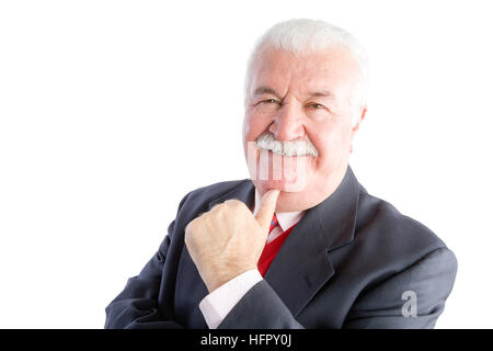 Portrait of smiling mature businessman in suit with hand under chin, white background - Stock Photo