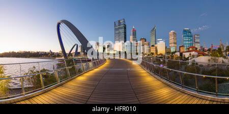 Twilight view along the Elizabeth Quay pedestrian bridge to the city skyline beyond, Perth, Western Australia, Australia - Stock Photo