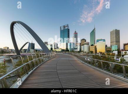 View along the Elizabeth Quay pedestrian bridge to the city skyline at twilight, Perth, Western Australia, Australia - Stock Photo