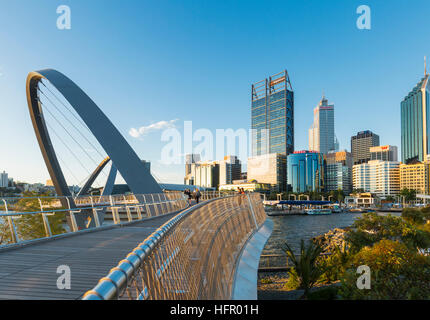 View along the Elizabeth Quay pedestrian bridge to the city skyline beyond at sunset, Perth, Western Australia, - Stock Photo