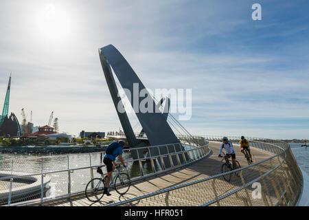 Early morning cyclists crossing the Elizabeth Quay pedestrian bridge, Perth, Western Australia, Australia - Stock Photo
