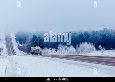 Semi-trailer truck headed for fog in the winter. - Stock Photo