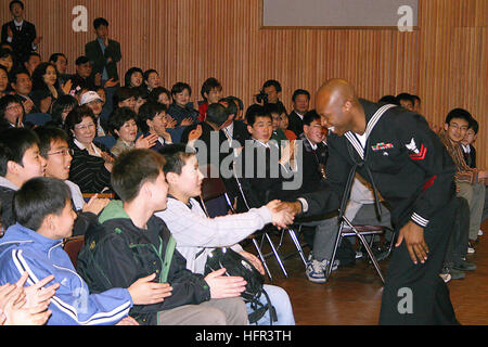 060320-N-2468S-001 BUSAN, Republic of Korea (March 20, 2006) --Musician 2nd Class Algie Smith shakes hands with - Stock Photo
