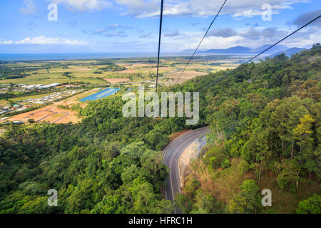 Kurana Skyrail Rainforest Cableway cable car going over a road  with the Cairns terminal in the distance. - Stock Photo