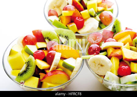 Fruit salad: kiwis, bananas, apples, peaches, mangoes, grapes and maraschino cherries - Stock Photo