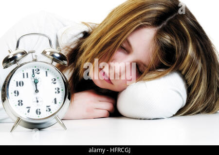 Girl dozing in front of an alarm clock - Stock Photo