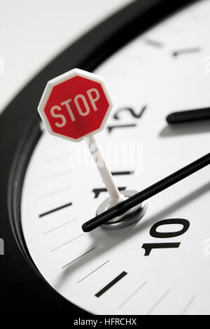 Stop sign on a clock: time standing still - Stock Photo