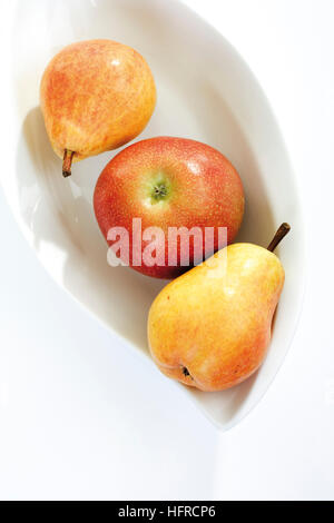 Red and yellow fruit, apple and two pears in a fruit bowl - Stock Photo