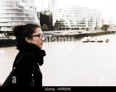 Young woman looks over the Thames, London, England, United Kingdom - Stock Photo