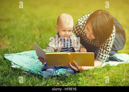 Smiling woman with short haircut laying on the grass and holding a book with her toddler - Stock Photo