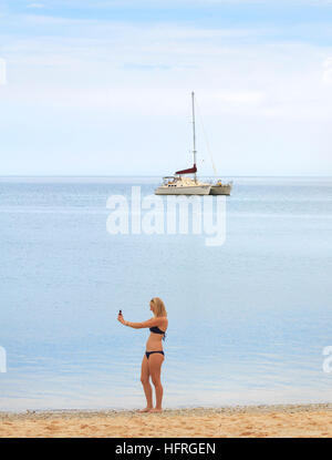 A girl in her early 20s taking a selfie on the beach with a catamaran yacht in the distance. - Stock Photo