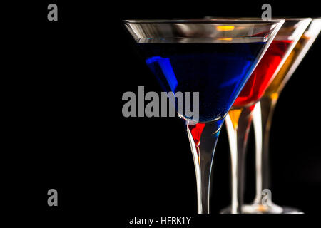 Colorful Cocktails in Martini Glasses on Black Background. Bar Commercials Concept. - Stock Photo