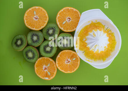 Up view of oranges and kiwis catted on half on green surface - Stock Photo