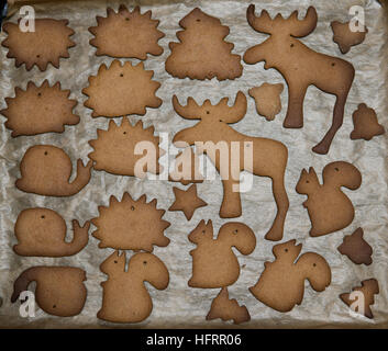 different shapes cutted out from a layer of gingerbread dough and baked - Stock Photo