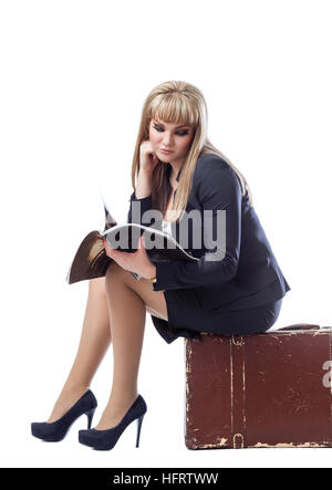 Beautiful young girl dressed in a business suit, sitting on a suitcase and reading a magazine. White isolated background. - Stock Photo