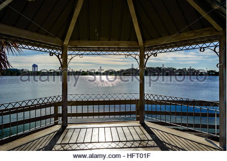 Photo showing the lake from inside the Gazebo and the sun glaring on the lake and floor. - Stock Photo