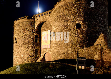 Carrickfergus Castle, built in the 12th century by Norman invaders, at night with the moon behind - Stock Photo