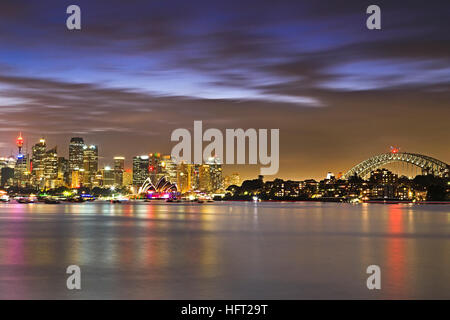 Panorama of SYdney city landmarks over Harbour from Bridge to Skysrapers and towers of CBD at sunset. - Stock Photo