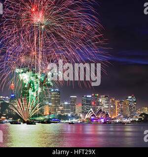 Close up view of Sydney New Year Eve Fireworks across Harbour above city CBD landmarks and towers. - Stock Photo